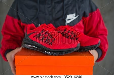Nike Sneakers Sportswear Close Up View. A Man Wearing Nike Windbreaker Jacket And Holding A Shoe Box