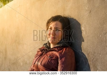 Brunette Woman With Red Leather Jacket Leaning To A Gray Concrete Wall Sitting Alone Under The Sunli