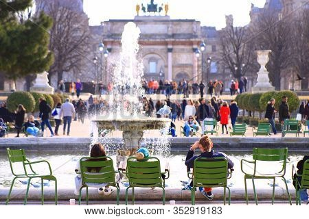 Paris, France. February 15. 2020. Group Of People Relaxing Sitting On Chairs In The Tuileries Garden