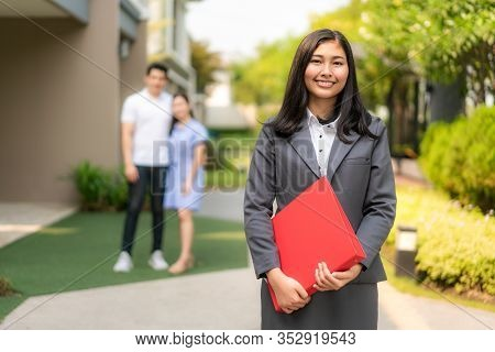 Asian Confident Woman Real Estate Agent Or Realtor In Suit Holding Red File And Smile With Young Cou