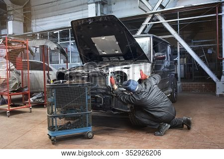 Professional Repair Worker In The Automotive Industry. Metal Car Body. Installs A New Aluminum Wing.