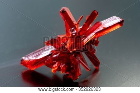 Red crystalline minerals on a black background