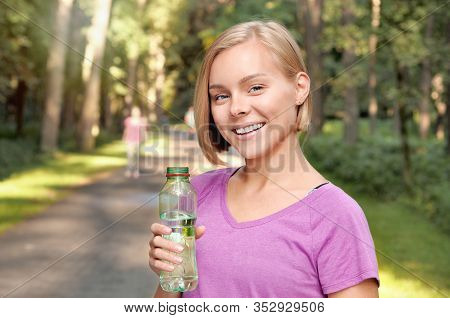 Young Blonde Girl Drinking Water During Morning Jogging