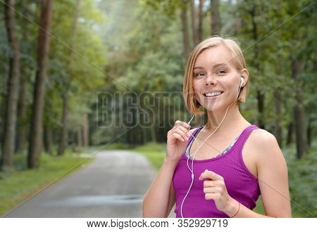 Portrait Of Young Smilling Sporty Woman Running With Headphones In The Fores Outdoor