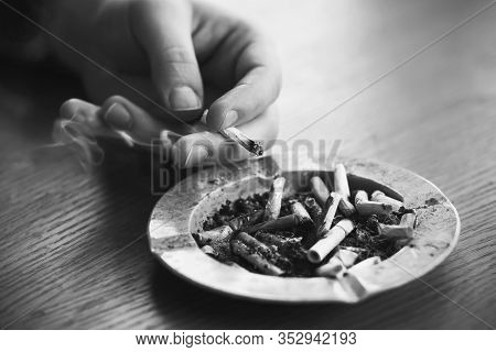 An Ashtray Filled With Cigarette Butts Stands On A Table, And A Hand Drops Ash From A Cigarette That