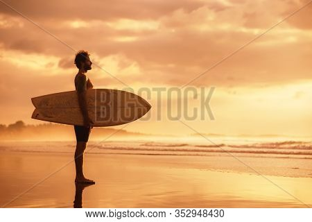 Attractive Sporty Real Surfer Stands With Surfboard At Sunset Ocean Beach