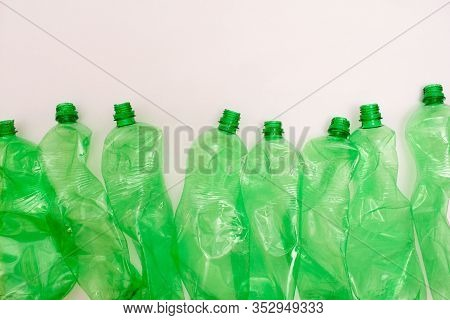 Used Plastic Green Bottle On White Background, Sorted Plastic Material For Waste Sorting And Recycli