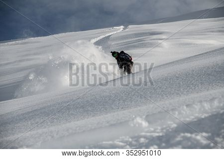 Freerider Glides Down The Mountain Side Covered In Snow