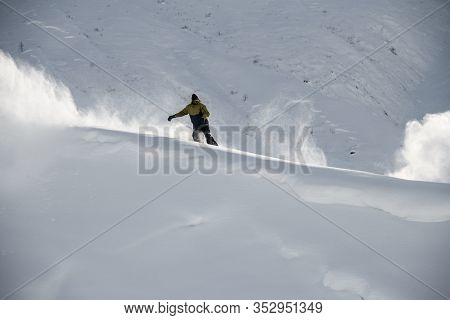 Male Freerider Slides On A Snowboard In Distance