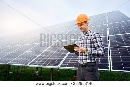 Worker In A Helmet Carries Out Work In A Tablet On The Background Of A Large Station Of Solar Panels