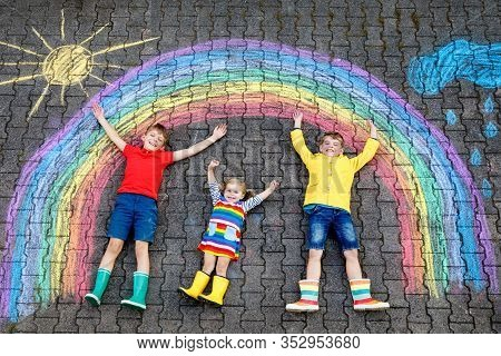 Three Little Children, Two School Kids Boys And Toddler Girl Having Fun With With Rainbow Picture Dr