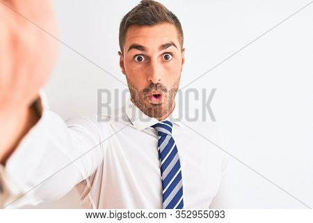 Young handsome business man taking selfie using smartphone over isolated background scared in shock with a surprise face, afraid and excited with fear expression