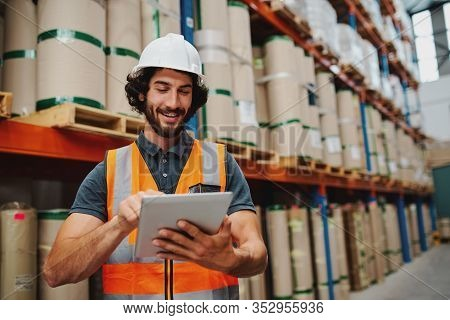 Male Warehouse Manager Adding Stock Inventory Data In Digital Tablet In Warehouse Wearing A White Ha