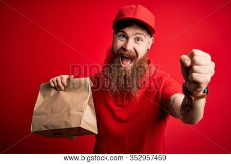 Redhead Irish delivery man with beard holding takeaway paper bag over red background screaming proud and celebrating victory and success very excited, cheering emotion
