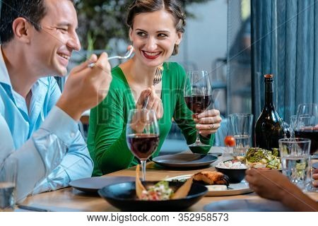 People having fun eating and drinking in a upscale restaurant toasting with red wine