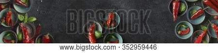 Chili Peppers With Basil And Peppercorns On A Rustic Surface