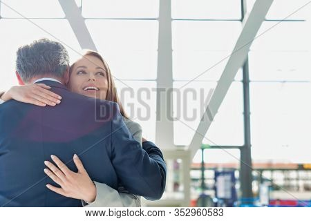 Business couple reuniting and embracing each other in the airport