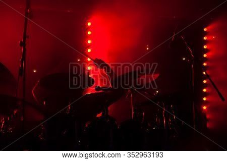 Silhouette Of A Drummer On Stage Under Red Lighting
