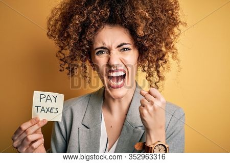 Young business woman with curly hair holding pay taxes to goverment reminder over yellow background annoyed and frustrated shouting with anger, crazy and yelling with raised hand, anger concept