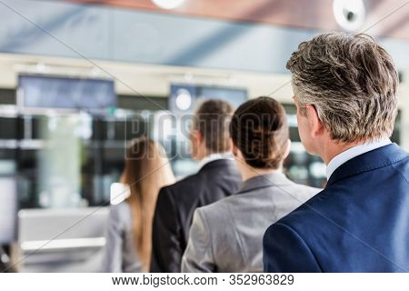 Business people queueing for check in at airport