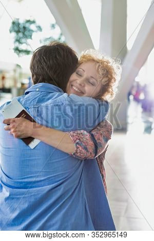 Wife reuniting with his husband in airport with lens flare