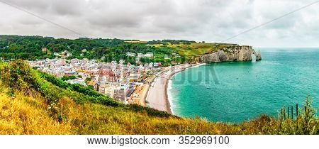 Panorama of Etretat town and natural chalk cliffs with visible arche, beach coastline and town, Normandy, France, Europe