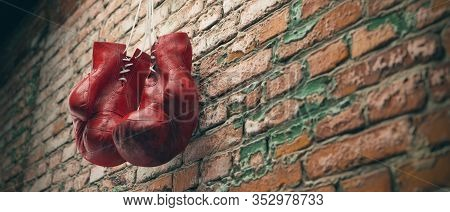 Old Red Boxing Gloves Hang On Nail On Brick Wall With Copy Space For Text. High Resolution 3d Render