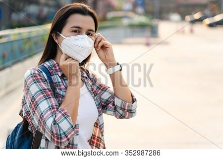 Asian Woman Wearing N95 Mask To Protect Pollution Pm2.5 And Virus. Covid-19 Coronavirus And Air Poll