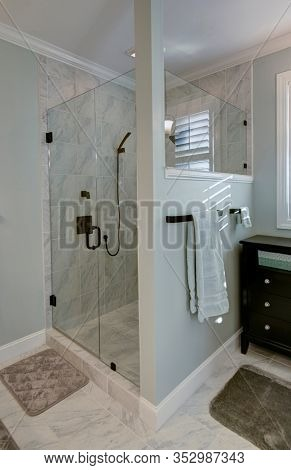 Beautiful stand alone glass shower with luxury marble tile and glass door.