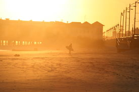 Surfer at the Beach Heading Home at Sunset