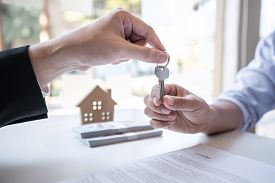 Sale Purchase Contract To Buy A House, Real Estate Agent Are Presenting Home Loan And Giving Keys To