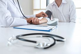 Doctor Using Stethoscope Checking Measuring Arterial Blood Pressure On Arm To A Patient In The Hospi