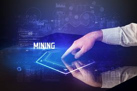 Hand touching digital table with MINING inscription, new age security concept