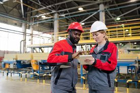 Content young multi-ethnic coworkers in hardhats using tablet while discussing manufacturing issues at construction plant