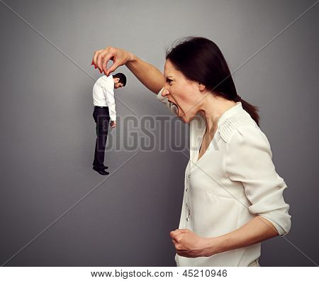 concept photo of big boss screaming at the small subordinate over dark background