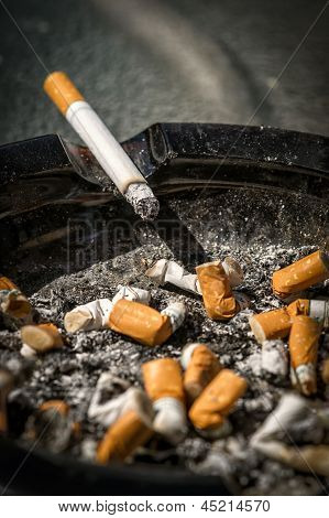 Cigarette On Side Of Dirty Ashtray