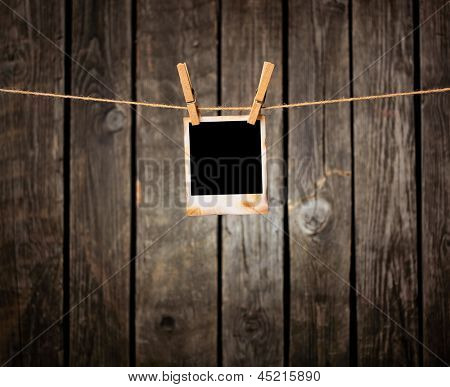 Blank instant photo hanging on the clothesline. On old wood background.