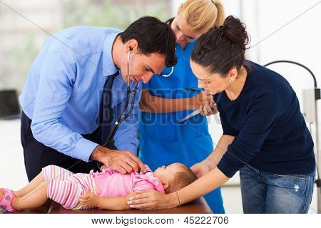 male pediatrician with nurse assistant examining a child in office
