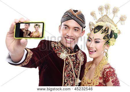 Casal de casamento feliz Java tradicional com telemóvel