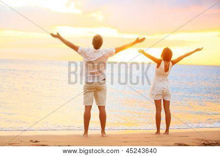 Gelukkig juichende paar genieten van zonsondergang op het strand met armen opgewekt in vrolijke opgetogen geluk. Happi