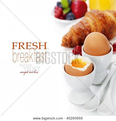 Delicious breakfast with eggs, fresh croissants, fructs and juice (with easy removable text)