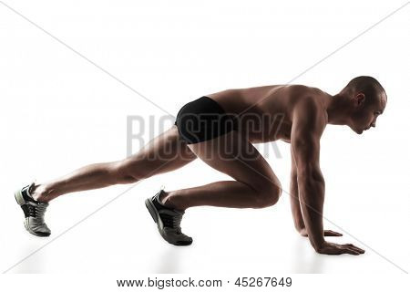 Young man getting ready to run, he is down in his runners stance, on white background