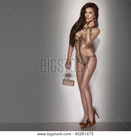 Elegant Brunette Lady Posing In Swimwear Looking Away.