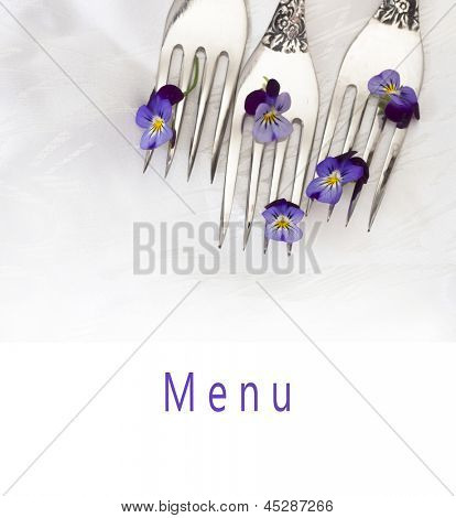 menu with silverware and fresh, wild violets