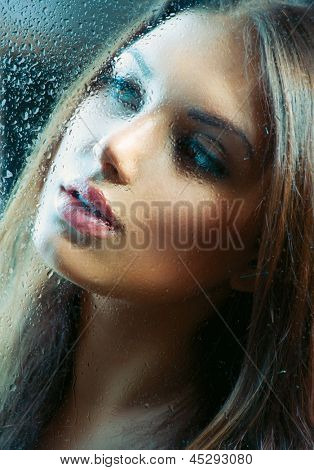 Portrait of Beauty Girl behind the Wet Glass. Melancholy Woman. Rain. Beautiful Model Looking Through the Window with Rain Drops poster
