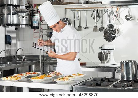 Young male chef with clipboard going through cooking checklist at commercial kitchen counter