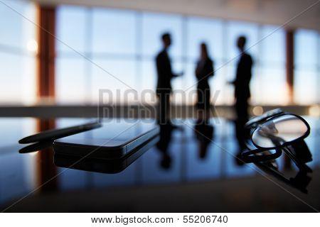 Nahaufnahme von Brillen, Handys und Stift am Arbeitsplatz auf Hintergrund Büroangestellte interagieren