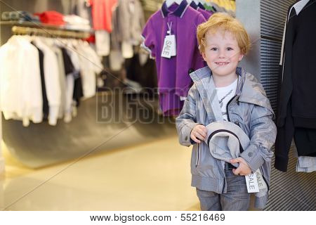 Smiling little boy stands near clothes hangers in children clothing shop.