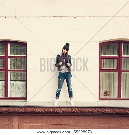 Young beautiful girl hipster is standing on cornice of house between two windows. Outdoors lifestyle. poster