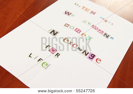 Letter to requirements of kidnapper on wooden table close-up